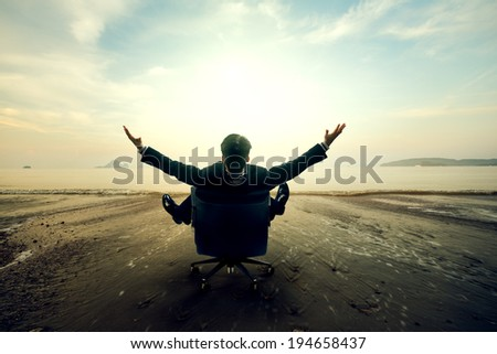 Relaxing businessman sitting on beach, Success in business concept