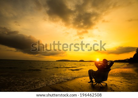 Relaxing businessman sitting on beach, Success in business concept - stock photo