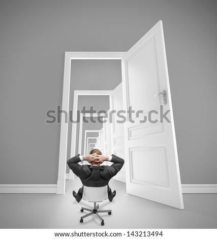 relaxing businessman sitting on chair and looking in opened doors - stock photo
