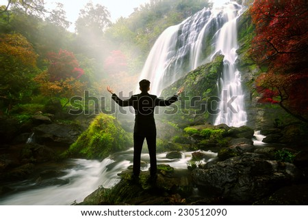 Relaxing businessman standing at waterfall, Success in business concept