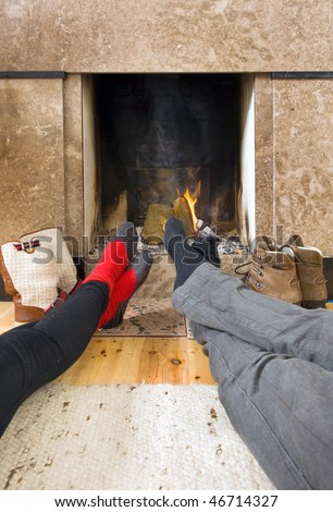 Relaxing by the fireplace - two pairs of feet warming near the fire after a long, cold, winter hike - stock photo