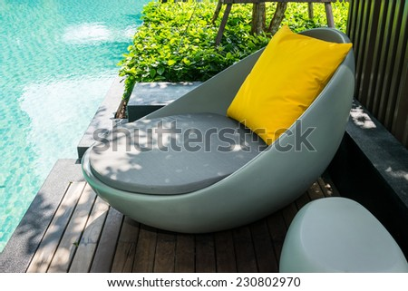 Relaxing chairs with pillows beside swimming pool - stock photo