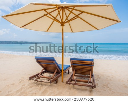 Relaxing couch chairs with parasol on white sandy Beach looking towards ocean and blue sky in Bali Indonesia
