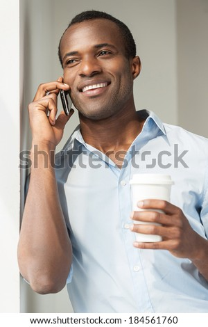 Relaxing during coffee break. Cheerful young African man in blue shirt holding a cup of coffee and talking on the mobile phone - stock photo