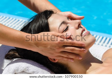 Relaxing facial massage in spa club at poolside. - stock photo