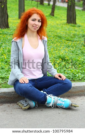 Relaxing ginger girl on skates in the park over beautiful green spring background - stock photo