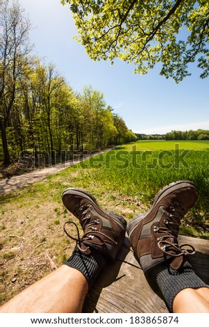 relaxing hiker with lifted hiking boots and view to a meadow in front of the forest, Odenwald, Germany, Europe - stock photo