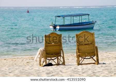 Relaxing holiday beach view with two chairs and a boat at a distance. Blue water and white sand.