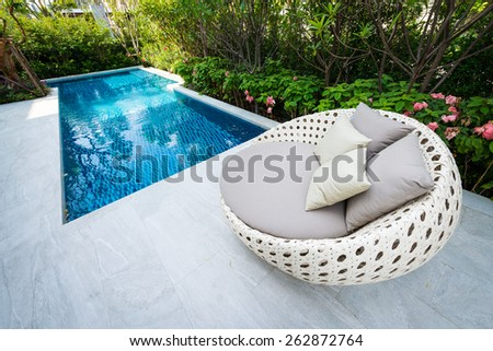 relaxing holiday by swimming pool with clear blue water / Empty sunbeds by the pool - stock photo