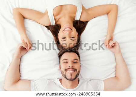 Relaxing in bed together. Top view of beautiful young loving couple lying in bed together and holding hands - stock photo