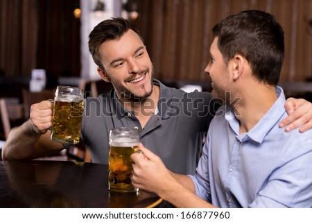 Relaxing in beer pub. Two cheerful young men drinking beer in bar - stock photo