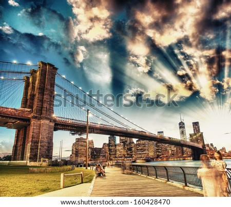 Relaxing in Brooklyn Bridge Park at summer sunset. Beautiful New York landscape. - stock photo