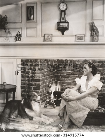 Relaxing in front of the fireplace with her collie - stock photo