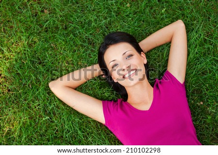 Relaxing in grass. Top view of beautiful young woman holding hands behind head and smiling to you while lying on the green grass - stock photo