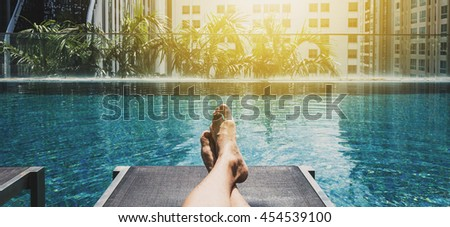 Relaxing in holidays, Asian guy feet on sun bathing bed at swimming pool in the city - stock photo
