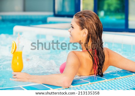 Relaxing in jacuzzi. Rear view of attractive young woman in bikini relaxing in jacuzzi - stock photo