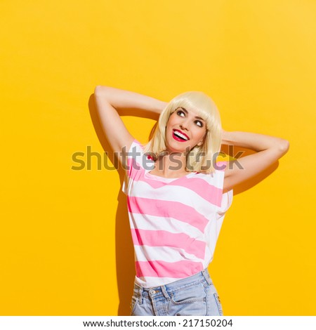 Relaxing in the sunlight. Happy blond young woman leaning on the wall with hands behind head and looking away. Waist up studio shot on yellow background. - stock photo