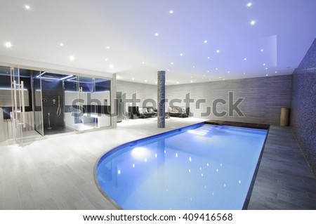 Relaxing indoor swimming pool with lighting and a corner for rest. Luxury resort swimming pool with beautiful clean blue water and  light effects around the swimming pool.  - stock photo