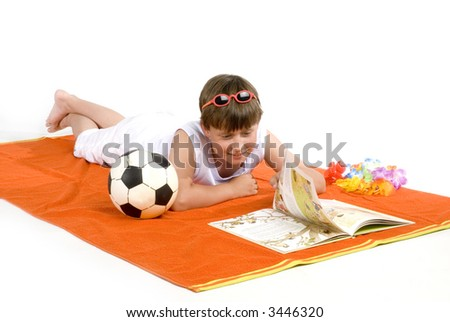 relaxing kid is reading a book after playing soccer