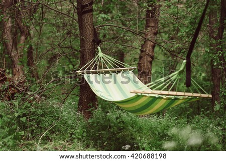 Relaxing lazy time with hammock in the green forest. Beautiful landscape with swinging hammock in the summer garden, sunny day outdoors. Travel, adventure, camping gear, nature outdoors items. - stock photo