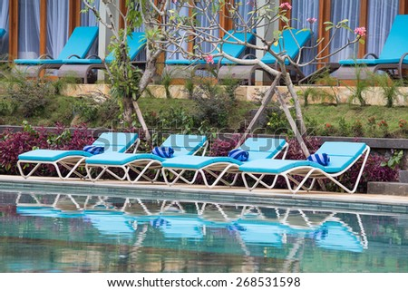 Relaxing lounge chairs by the swimming pool - stock photo