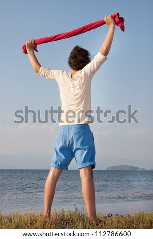Relaxing male with red towel at sea side - stock photo