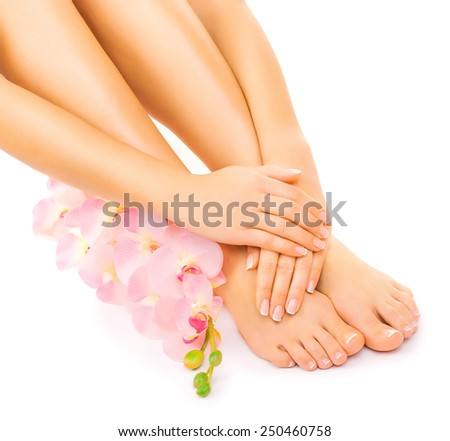 Relaxing manicure and pedicure with a pink orchid flower - stock photo