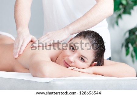 Relaxing massage for young beautiful woman at spa - stock photo
