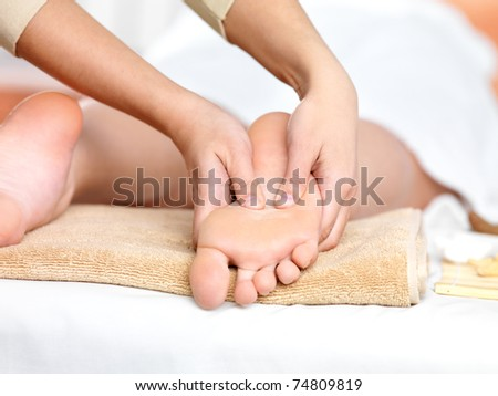 Relaxing massage on the foot  in spa salon - indoors