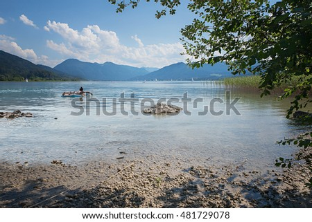 relaxing on a air mattress at lake tegernsee, bavarian summer landscape