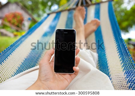 relaxing on hammock with a smartphone  - stock photo
