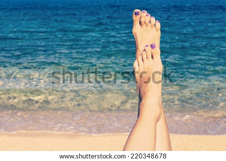 Relaxing on the beach with legs up. Sexy legs. Retro look - stock photo