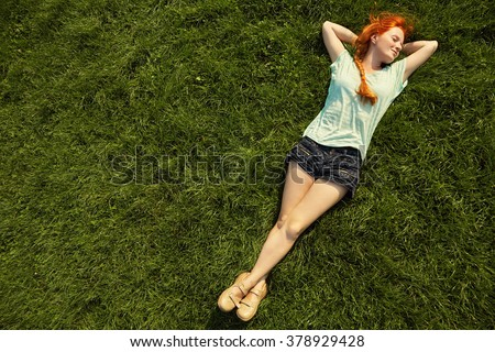 relaxing redhead girl lying on the grass. woman relaxation outdoor - stock photo