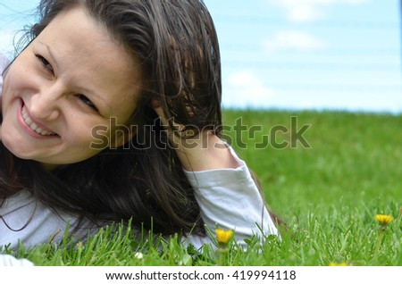 Relaxing spring day- pretty girl enjoys lying on the grass. Healthy lifestyle - stock photo