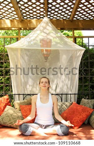 Relaxing teenager doing yoga on a couch full of cushions outside