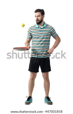 Relaxing tennis player in polo shirt balancing ball with racket. Full body length portrait isolated over white studio background. - stock photo