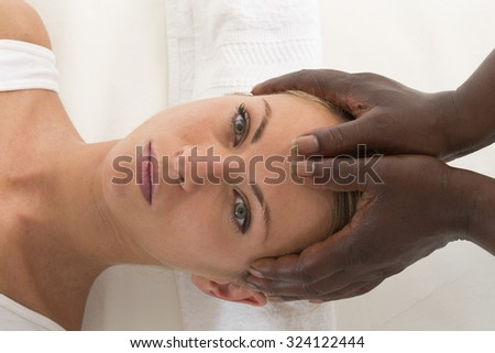 Relaxing therapy: Beautiful Woman Receiving Head massage  - stock photo