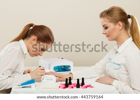 Relaxing time and wellness day concept. Blonde elegant woman visiting professional manicurist salon. Beautician makes perfect nails to client.