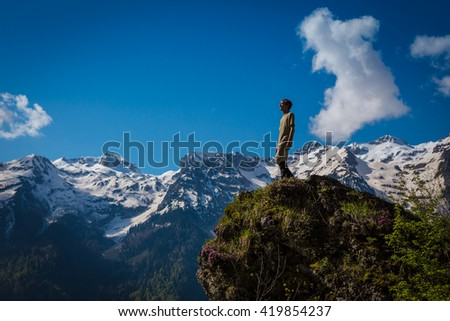 Relaxing tourist on mountain cliff outdoors. Photo man traveler with mountains on background. Lifestyle travel concept Summer vacations.
