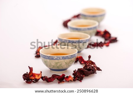 Relaxing with a cup of tea. Image of a row of tea cups surrounded by flower tea composition isolated on white background with selective focus - stock photo