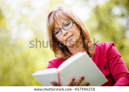 Relaxing with a good book.Smiling mature woman reading a book in the park.