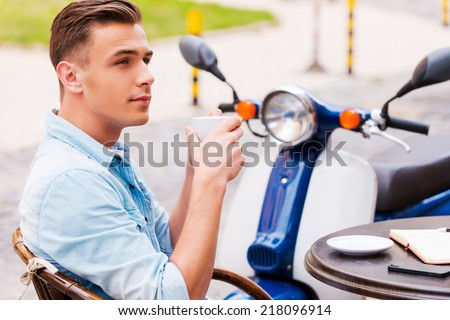 Relaxing with cup of fresh coffee. Side view of relaxed young man drinking coffee while sitting in sidewalk cafe with scooter in the background - stock photo