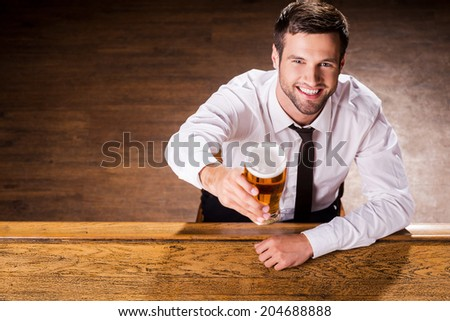 Relaxing with glass of fresh beer. Top view of handsome young man in shirt and tie holding glass with beer and smiling while sitting at the bar counter  - stock photo