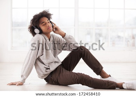Relaxing with his favorite music. Cheerful African teenager in headphones listening to the music and keeping eyes closed while sitting on the floor - stock photo