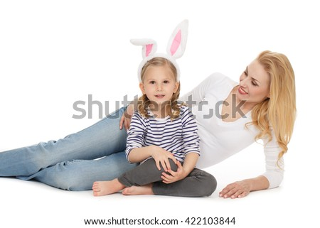 Relaxing with little bunny. Adorable mature woman lying next to her little daughter wearing bunny ears and looking to the camera cheerfully at the studio on white background. - stock photo