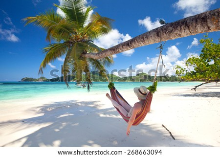 relaxing Woman in a hammock on a tropical beach - stock photo