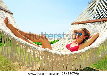 Relaxing Woman in a hammock on a tropical beach. Vacation concept