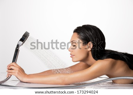Relaxing woman in bathroom holds the shower in hands  with stream of water - stock photo