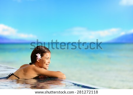 Relaxing woman in luxury hotel pool on holidays vacation travel. Asian young female person enjoying in pool spa at hotel resort in an exotic paradise getaway. - stock photo