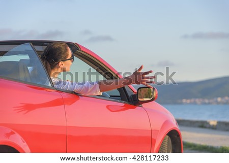 Relaxing woman on the beach in the cabriolet car without a roof. Vacation, holiday, journey to the sea or the resort.
